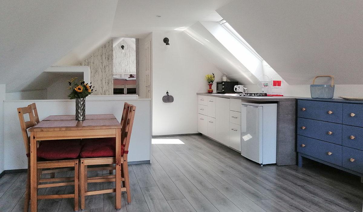 V zgornjem nadstropju se prostor odpre v praktično urejeno kuhinjo z jedilno mizo in se nadaljuje v udoben dnevni prostor.