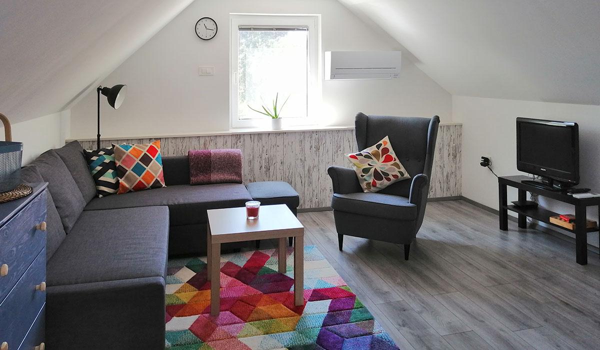 Udoben dnevni prostor s kotno garnituro, naslanjačem in televizijo